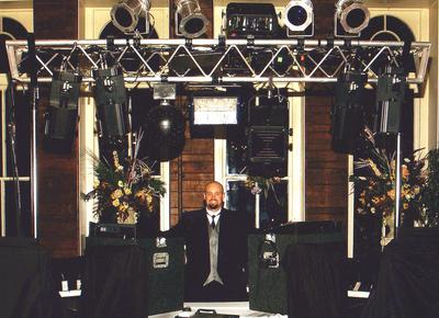 This is Emcee Sean Hearn in Eureka Springs at the Crescent Hotel in the early 2000s, standing under his immense lighting array that included several par cans, a 2000 watt black light, 4 Martin 812 intelligent scanners, an Atomic Strobe, a Martin Rapture and a fog machine. These lights paired with his Peavey SP2 speakers and 118 Black Widow sub woofer is a crystal clear sounding and visually stunning display.