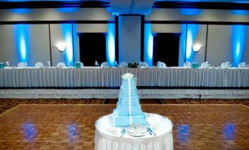 A beautiful setting at a reception that highlights the baby blue uplights that were intentionally chosen to match the bridal colors and the the color of the icing on the wedding cake.
