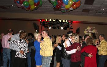 Party guests dance under the ballons at the New Years Eve Gala at the Inn of the Ozarks Best Western