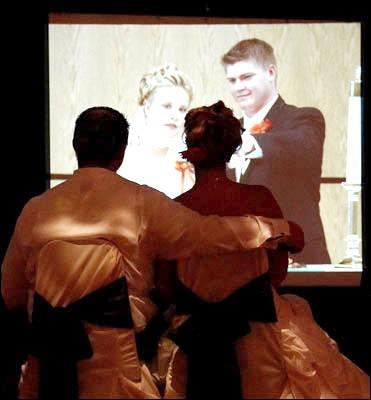 Newlyweds sit, holding hands as they and their guests watch pictures from their childhood and courtship on a 15 foot video screen provided by Sean Hearn with Music In Motion.