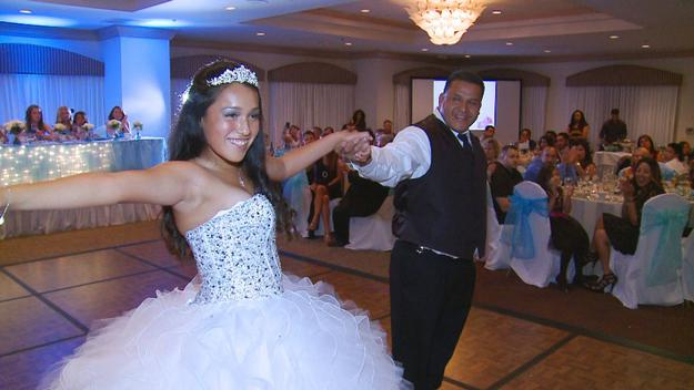 A proud father dances with his little princess dressed in a stunning white sequin gown and diamond tiara at at her Quinceanera.