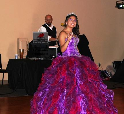 Beautiful young Hispanic girl dressed in a pretty purple sequin dress dances at her Quinceanera at the Event Place in Fayetteville, AR.