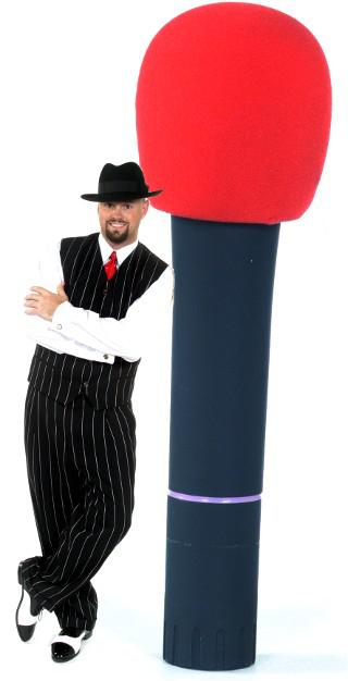 Disk Jockey Sean Hearn appears to be standing beside a life size cordless Shure Microphone. Sean is always dressed for the occasion and in this case is wearing a pin striped zoot suite, black and white spat shoes, a sharp black fedora hat, a bright red tie and a pair of sterling silver gramophone record player cuff links.