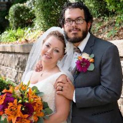 Amber Benabeh with her new husband holding a fall colored floral bouquet.