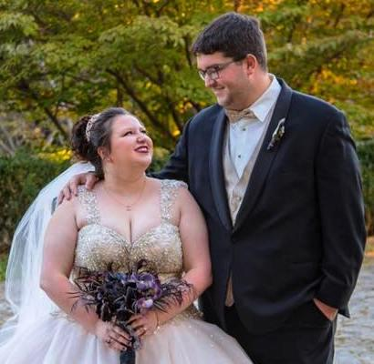 Madison McDonald with her new husband in her wedding gown holding a large bouquet.