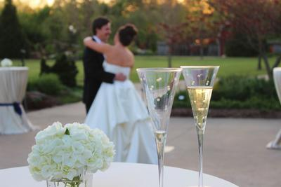 Bride and groom waltz to their first dance song at the Botanical Gardens in Fayetteville, AR, behind the 2 champagne glasses that they used to share their toast after the cake cutting.